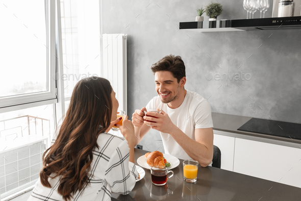 Portait of pleased couple looking at each other and smiling, whi - Stock Photo - Images