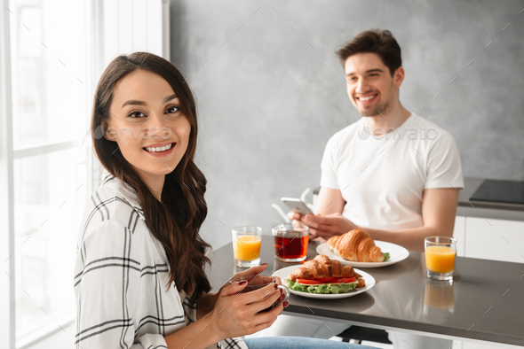Portait of joyous man and woman 30s having breakfast or dinner i - Stock Photo - Images