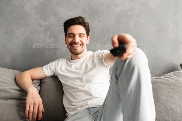 Smiling man 30s in casual t-shirt sitting on sofa in living room - Stock Photo - Images