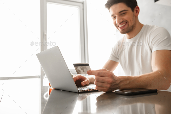 Photo of joyous adult man 30s in casual clothing holding credit - Stock Photo - Images