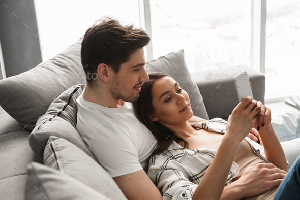 Portrait of gorgeous people man and woman lying on sofa at home, - Stock Photo - Images