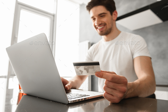 Photo of successful man 30s in casual clothing holding credit ca - Stock Photo - Images