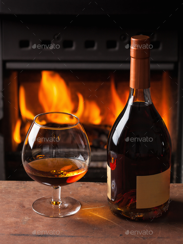 a glass of cognac in front of fireplace - Stock Photo - Images