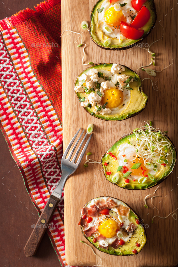 eggs baked in avocado with bacon, cheese, tomato and alfalfa spr - Stock Photo - Images