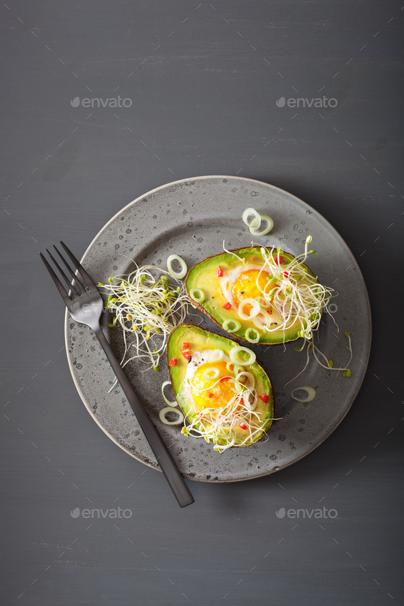 egg baked in avocado with spring onion and alfalfa sprouts - Stock Photo - Images