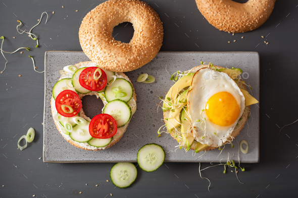 sandwiches on bagels with egg, avocado, soft cheese, tomato, cuc - Stock Photo - Images