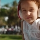 Cute Caucasian Girl with Curly Hair, in White Dress Sits in Park in White Headphones, Listen To - VideoHive Item for Sale