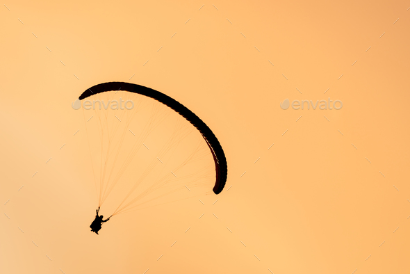 Silhouette of paraglider tandem flying in orange sky - Stock Photo - Images