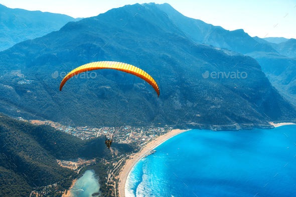 Paraglider tandem flying over the sea with blue water and mountains - Stock Photo - Images
