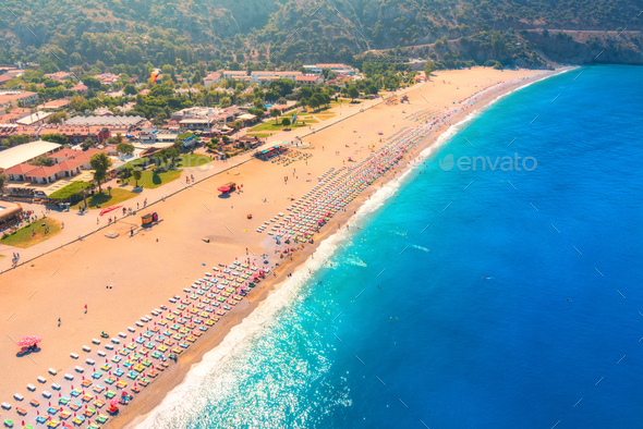 Aerial view of sandy beach with colorful chaise-lounges and blue sea - Stock Photo - Images