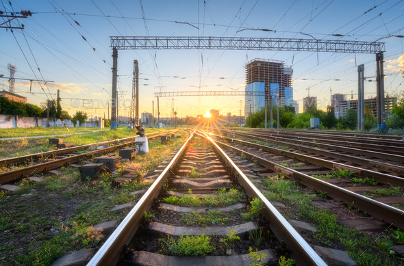 Industrial landscape with railway station, green grass, buildings - Stock Photo - Images