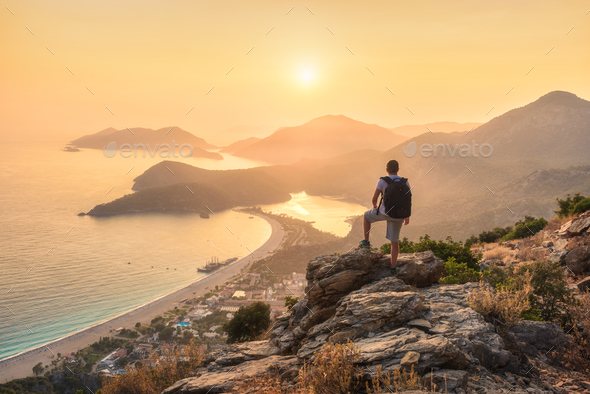 Young sporty man with backpack, seashore and mountains - Stock Photo - Images