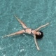 Beautiful Young Woman Floating in Crystal Clear Water, Aerial Rotating Shot - VideoHive Item for Sale