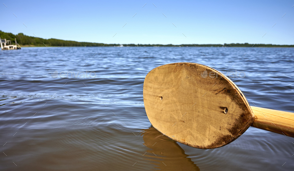 Wooden paddle over water. - Stock Photo - Images