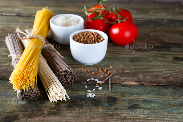 bunch of Italian spaghetti, noodles soba and sommel, bowls with buckwheat and rice with tomato - Stock Photo - Images