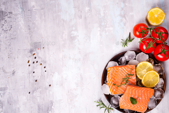 Salmon steaks on ice with lemon slice on wooden plate with tomato - Stock Photo - Images