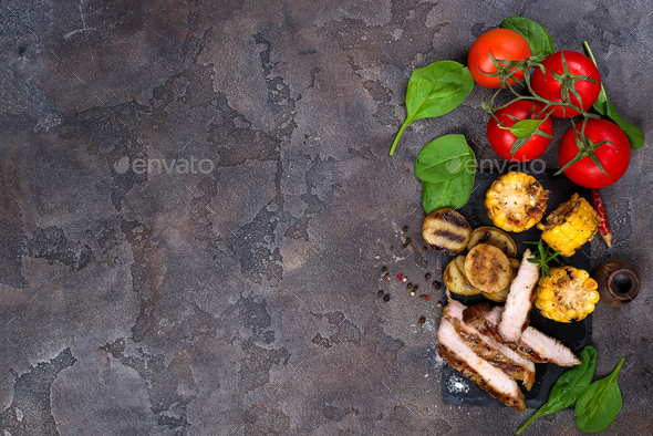 sliced pork steak and grilled vegetables on slate board on stone table. - Stock Photo - Images
