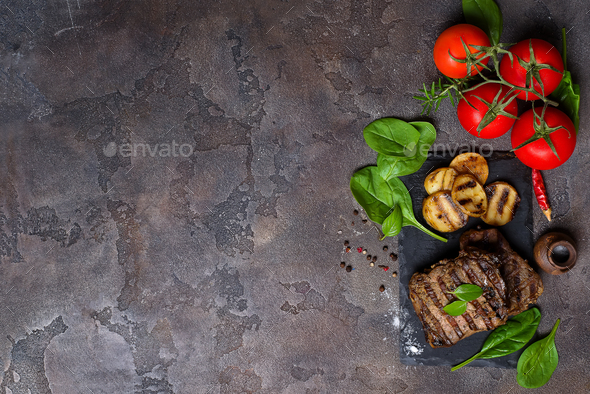 Beef steak and grilled vegetables on slate board on stone table. - Stock Photo - Images