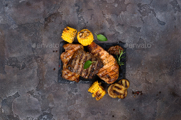 Fresh three types of grilled steak on slate plate with herbs and grilled potatoes - Stock Photo - Images