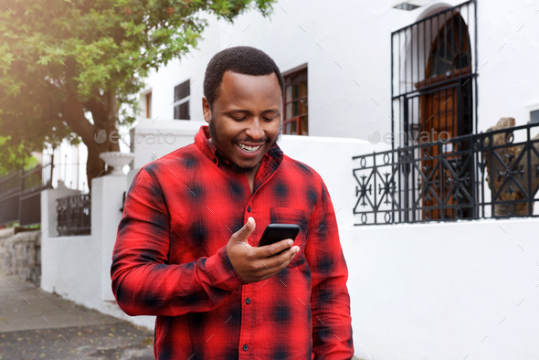 cool black guy smiling outside with cell phone - Stock Photo - Images