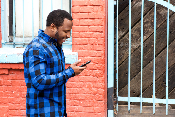 young black man walking in city with mobile phone - Stock Photo - Images