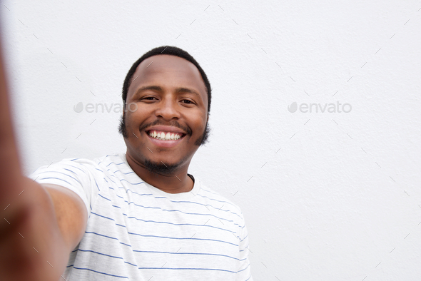 smiling young african american man taking selfie - Stock Photo - Images