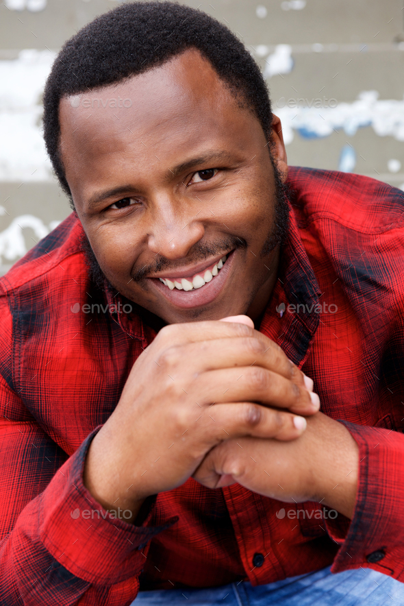 smiling young african american man with hands together - Stock Photo - Images