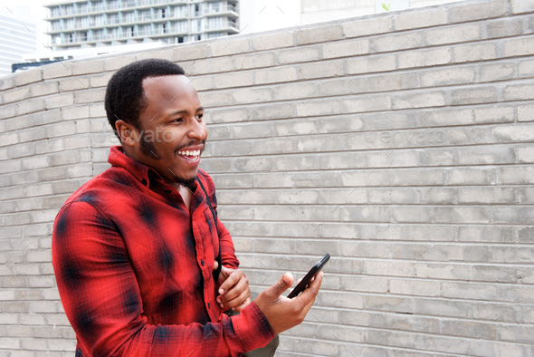 happy young black man walking with mobile phone - Stock Photo - Images
