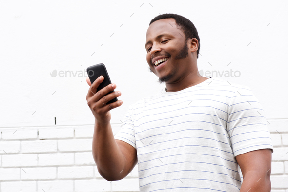 cool smiling young black man looking at mobile phone - Stock Photo - Images