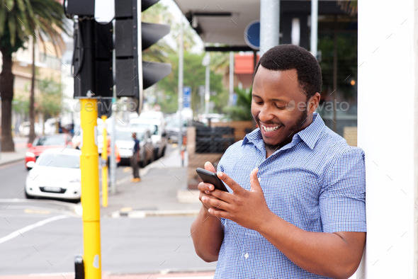 smiling young man standing in city with cellphone - Stock Photo - Images