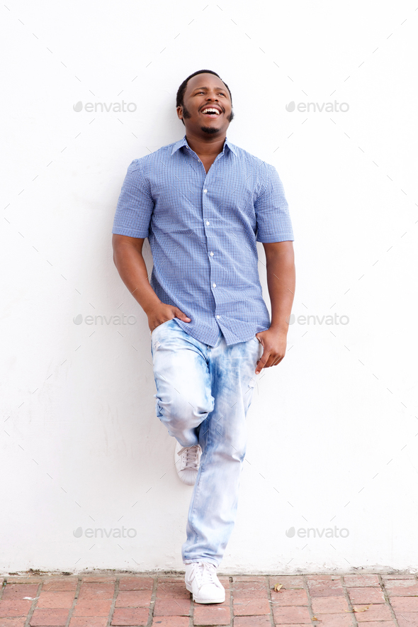 young man laughing and leaning against white wall - Stock Photo - Images