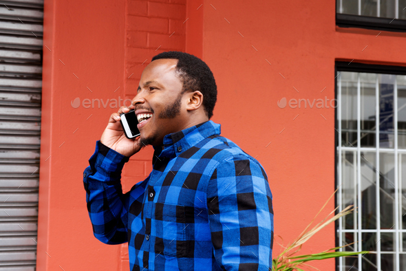 young african american man walking and talking on mobile phone - Stock Photo - Images