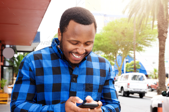 african man smiling and looking at cell phone in the city - Stock Photo - Images