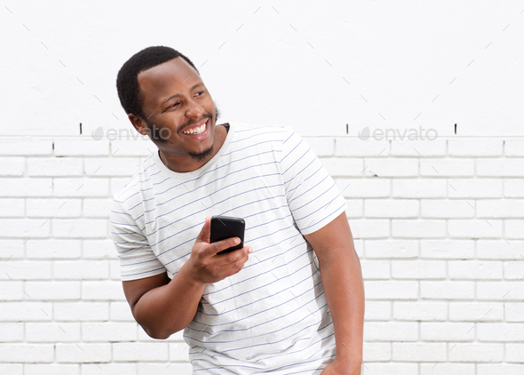 cool black guy smiling with cellphone against white wall - Stock Photo - Images