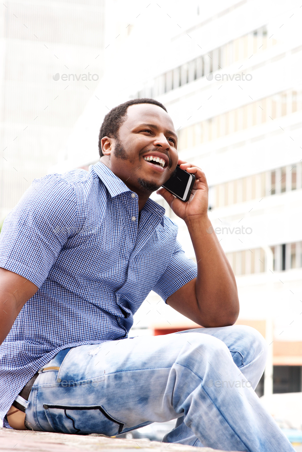 young man sitting in city talking on cellphone - Stock Photo - Images