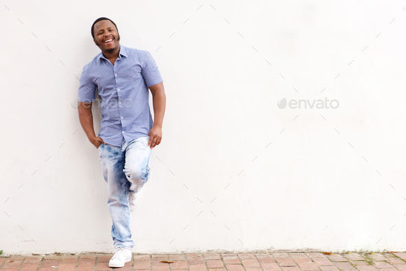 smiling african american man leaning against white wall - Stock Photo - Images