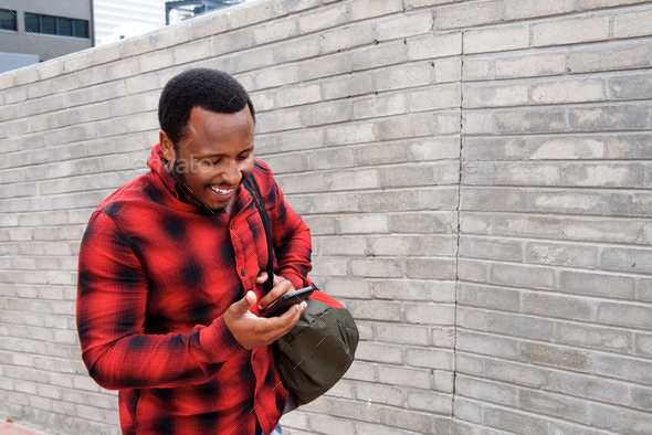 young black man walking with mobile phone and bag - Stock Photo - Images