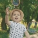 Little Boy in Hat Catching Bubbles. Little Child Playing with Parents Outside - VideoHive Item for Sale