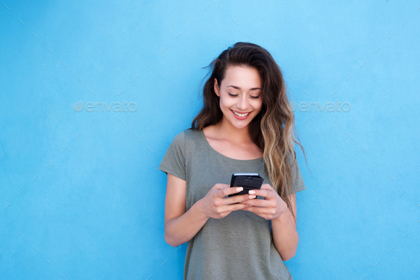 young smiling woman using mobile phone against blue background - Stock Photo - Images