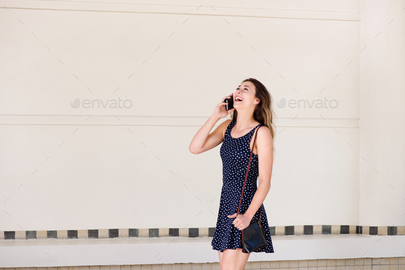 young happy woman walking outside talking on mobile phone - Stock Photo - Images