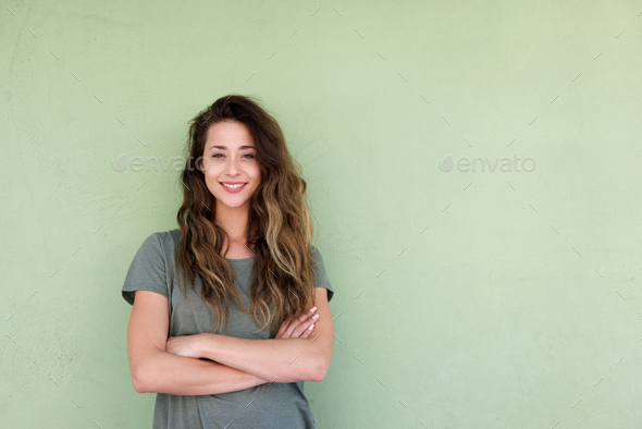 young smiling woman with arms crossed against green background - Stock Photo - Images
