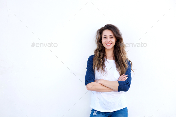 young happy woman standing with arms crossed on white background - Stock Photo - Images