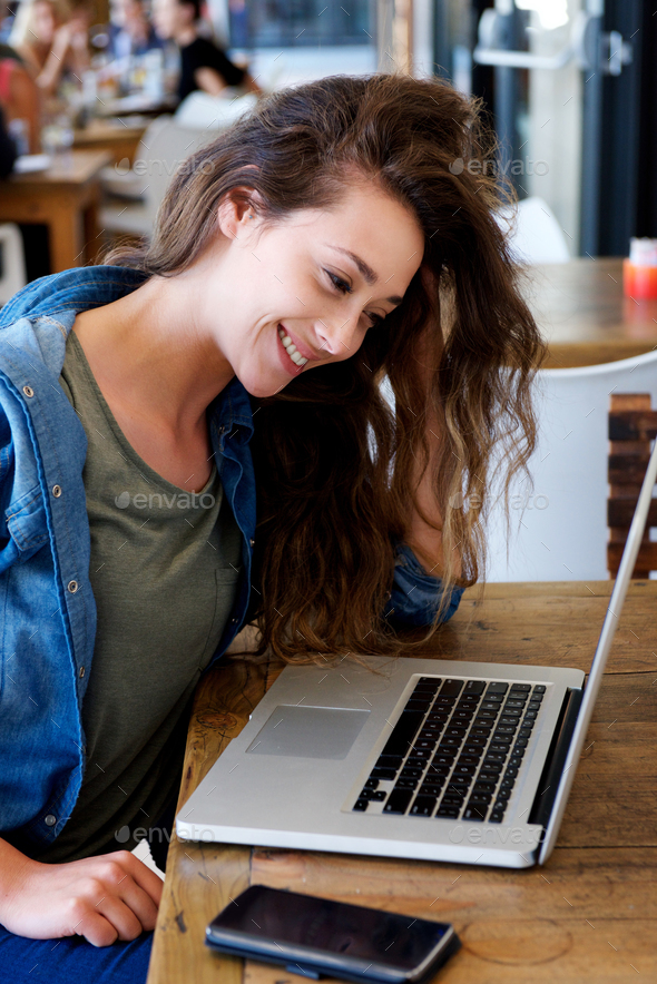 young happy woman sitting at cafe using notebook - Stock Photo - Images