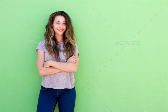happy young woman standing with folded arms - Stock Photo - Images