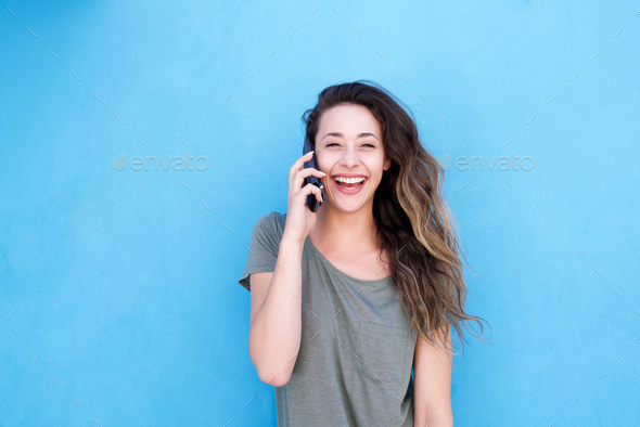 laughing woman talking on cellphone against blue background - Stock Photo - Images