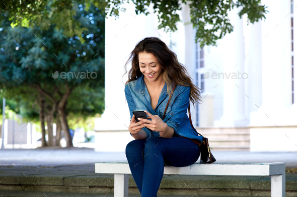 smiling young woman sitting on bench using mobile phone - Stock Photo - Images