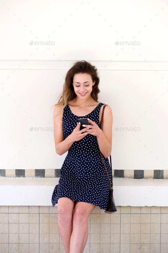 happy woman relaxing outside with smart phone - Stock Photo - Images