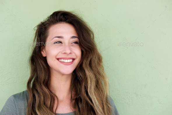 young beautiful woman on green background smiling - Stock Photo - Images