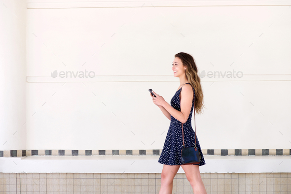 happy woman walking with handbag and  mobile phone - Stock Photo - Images