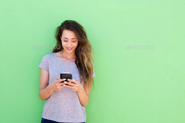 beautiful young woman holding smart phone on green background - Stock Photo - Images
